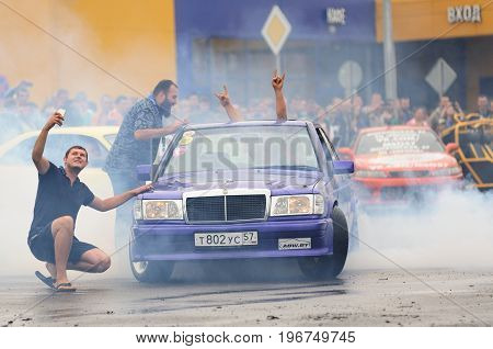 Orel Russia July 22 2017: Dynamica car festival. People have fun and make selfie near tuned car in burning wheel smoke clouds on wet asphalt