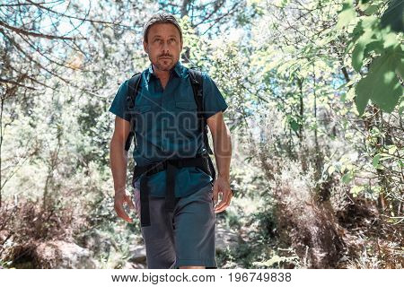 Male Backpacker With Long Blond Hair Walking In Forest.