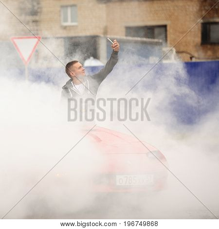 Orel Russia July 22 2017: Dynamica car festival. Young man making selfie in burning wheel smoke clouds with industrial background