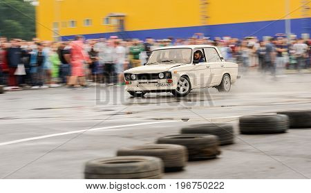 Orel Russia July 22 2017: Dynamica car festival. Tuned white vintage Russian VAZ Lada car drifting in water puddles at rainy day