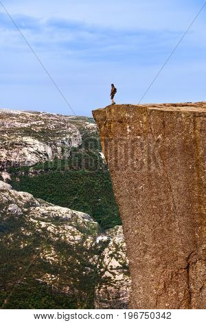 Lonely man standing on cliff Preikestolen in fjord Lysefjord - Norway - nature and travel background
