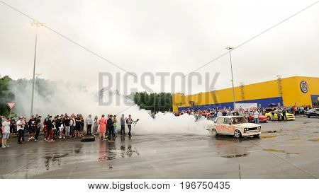 Orel Russia July 22 2017: Dynamica car festival. Tuned vintage Russian VAZ Lada car drifting in burning wheel smoke clouds panoramic view