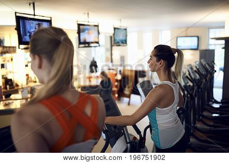 Side view of middle-aged woman using anaerobic exercise machine in gym