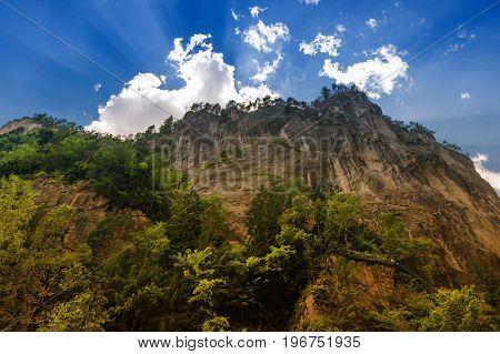 Huge rock wall, the sunshine breaks through behind