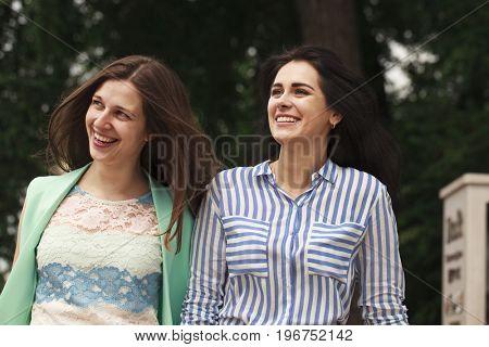 Two happy women walking in the summer park
