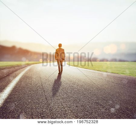 Man walks on an unknown road for a new adventure at sunset. Concept of new opportunities