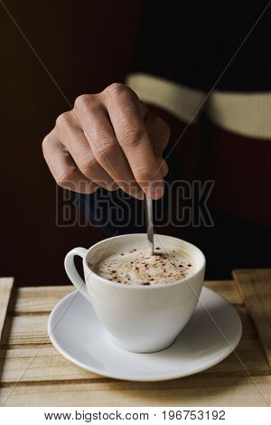 closeup of a young caucasian stirring a cup of cappuccino with a spoon, sitting at a rustic wooden table