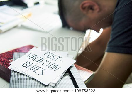 closeup of a concerned man sitting at his office desk and a note in the foreground with the text post-vacation blues handwritten in it