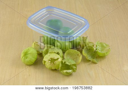 Food preparation of dehusked tomatillos in plastic refrigerator storage container with separated husks on the side