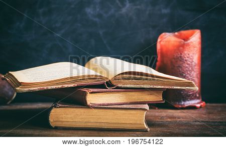 Vintage Books And Candle On Blackboard Background