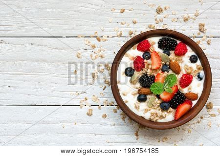 bowl of greek yogurt with granola oats berries and nuts for healthy breakfast. top view