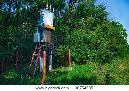 Old Working Rural Electrical Distribution Transformer In The Forest. Sunny Day, The Concept Of Indus
