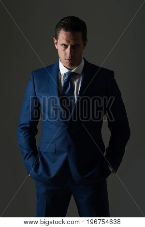 man businessman or manager with serious face and stylish hair haircut posing in fashionable blue formal suit on grey background. Business fashion and success