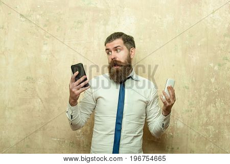 man or hipster with long beard and stylish hair on scared face in tie and white shirt on beige background compare mobile phone and smartphone conversation and information businessman