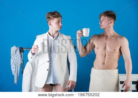 Men posing with cups. Businessman wearing shirt jacket and underpants. Macho with muscular torso wrapped in white towel. Clothes rack on blue background. Fashion and fitness concept.