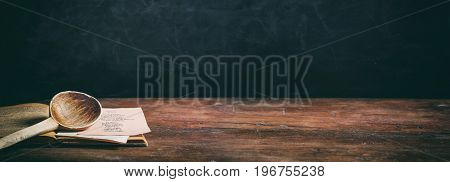 Wooden Spoon And A Cooking Recipe On Wooden Background