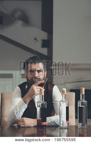 Hipster drinking red wine alone in restaurant. Brutal man with beard sitting at table with three bottles and glass. Alcohol abuse. Addictive and convive. Unhealthy lifestyle and bad habits