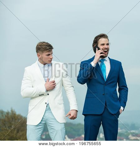 Businessman smiling and talking on mobile phone. Men wearing formal suits. Boss and employee on sunny day. Director with bodyguard on blue sky. Security service and technology concept.