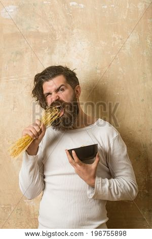 man or bearded hipster eating raw pasta or macaroni and holding bowl on textured wall background