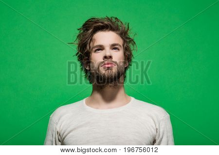handsome man with beard and stylish hair in white underwear on green background morning and fashion
