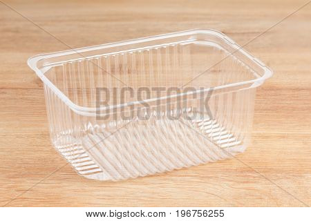 Plastic container for foodstuffs. Isolated on wooden background.