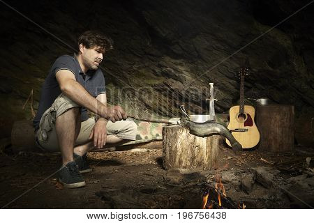 Man relaxing in wilderness with guitar and preparing hunted fish