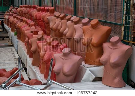 A large group of dummies in a store on the market.  Mannequins are deprived of clothes and put in two rows.