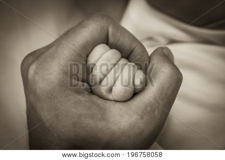 Father holding his newborn baby hand  in fist symbolizing love and care