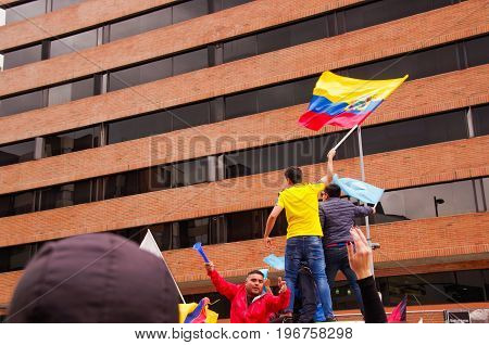 Quito, Ecuador - April 7, 2016: Unidentified people with ecuadorian and white flags supporting the presidential candidate Guillermo Lasso, and journalists during anti government protests in Shyris Avenue.