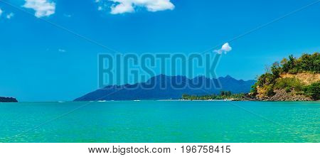 Seascape with islands on the horizon in Pantai Tengah Beach, Langkawi Island, Malaysia. The blue lagoon on the tropical coast of the Andaman Sea