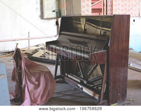 Brown Grand Piano With The Lid Open And The Chair In The Room Among The Dust, Dirt And Debris In An
