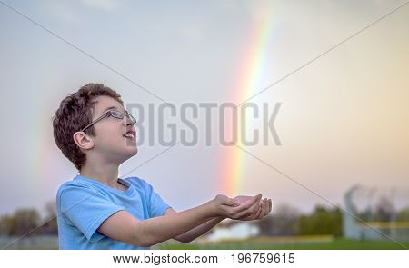Young boy looking up in awe at bright rainbow after spring rain trying to catch the colors in his hands outdoors childhood and wonder concepts