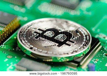 Silver Bitcoin virtual currency on a circuit board background