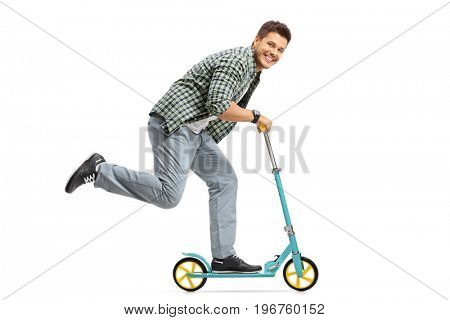 Young guy riding a scooter and looking at the camera isolated on white background