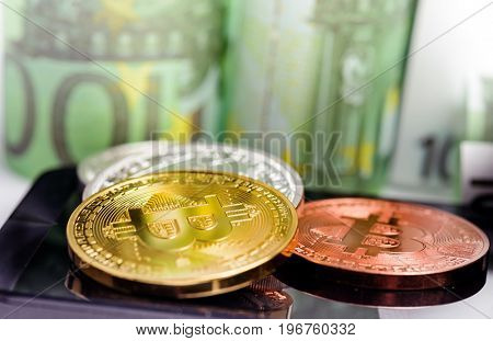 Bitcoin coins on smartphone over Euro banknotes money background