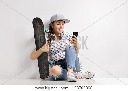 Teenage girl with a skateboard using a phone and sitting on the floor