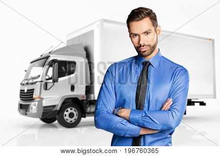 Handsome businessman standing in front of a truck, isolated on white. Transport and distribution.