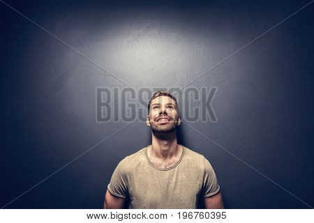 Attractive, smiling man leaning against the wall. Hapiness and positive attitude. Vintage look.