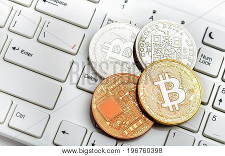 Bitcoin coins gold and silver on white keyboard background