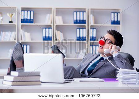 Clown businessman talking on phone working in office