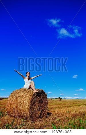 beautiful woman in the harvested  wheat field in august on a sunny day