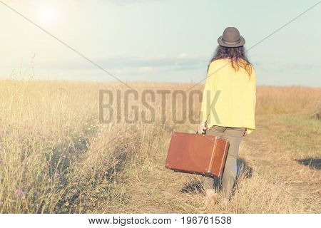 Beautiful young woman with black hat carries brown vintage suitcase in the field road during summer sunset. Back view. Toned image and travel concept.