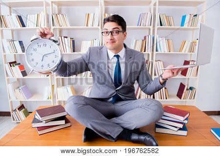 Businessman student in lotus position with an alarm clock and a
