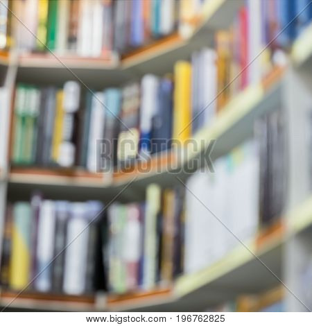 Abstract blurred books, manuals and textbooks on bookshelfs in library or in book store, for backdrop. Concept of education