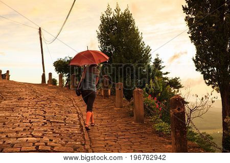 MOTOVUN CROATIA - JULY 12: Woman with umbrella walking on typical stone street of the town on July 12 2017