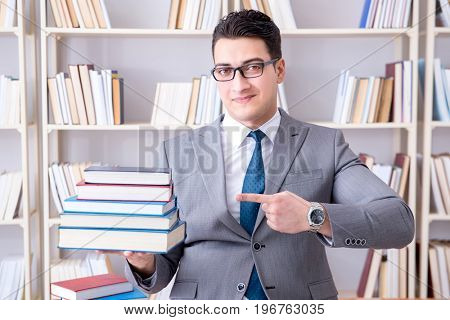 Business law student with pile of books working in library