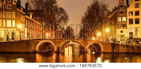 Amsterdam by night. Illuminated bridge over water canal, gracht. Netherlands