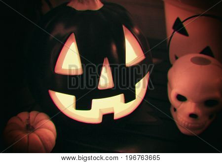 Vintage filtered image of a halloween Jack o lantern glowing in the evening to greet trick or treaters