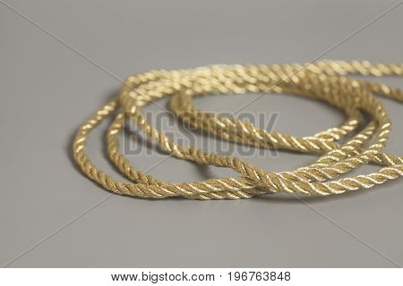 Golden rope on a gray background .