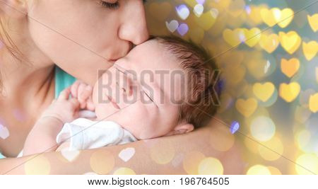 Mother kissing baby on Christmas lights background